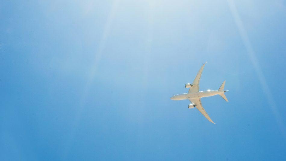 Passenger jet airplane flying on blue sky with sunlight